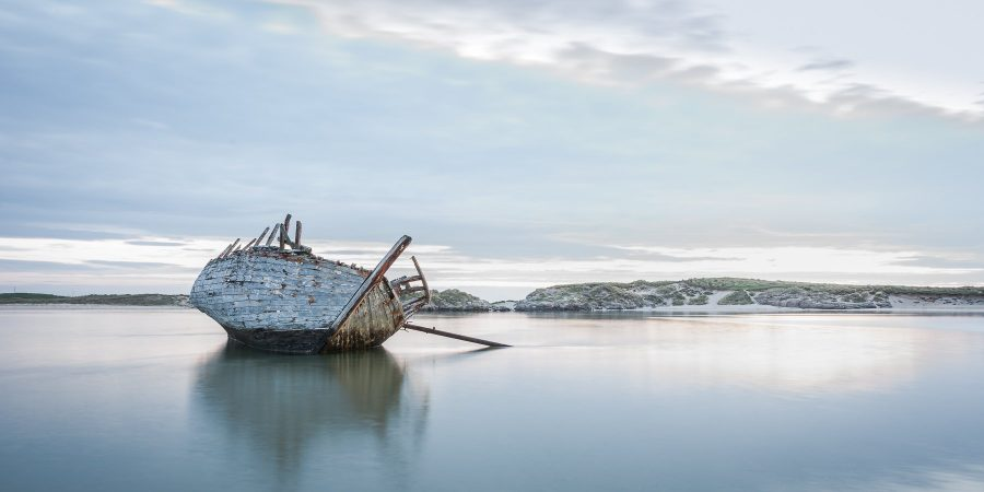 Dilapidated wooden ship Bad Eddie on leaning on its side at low tide