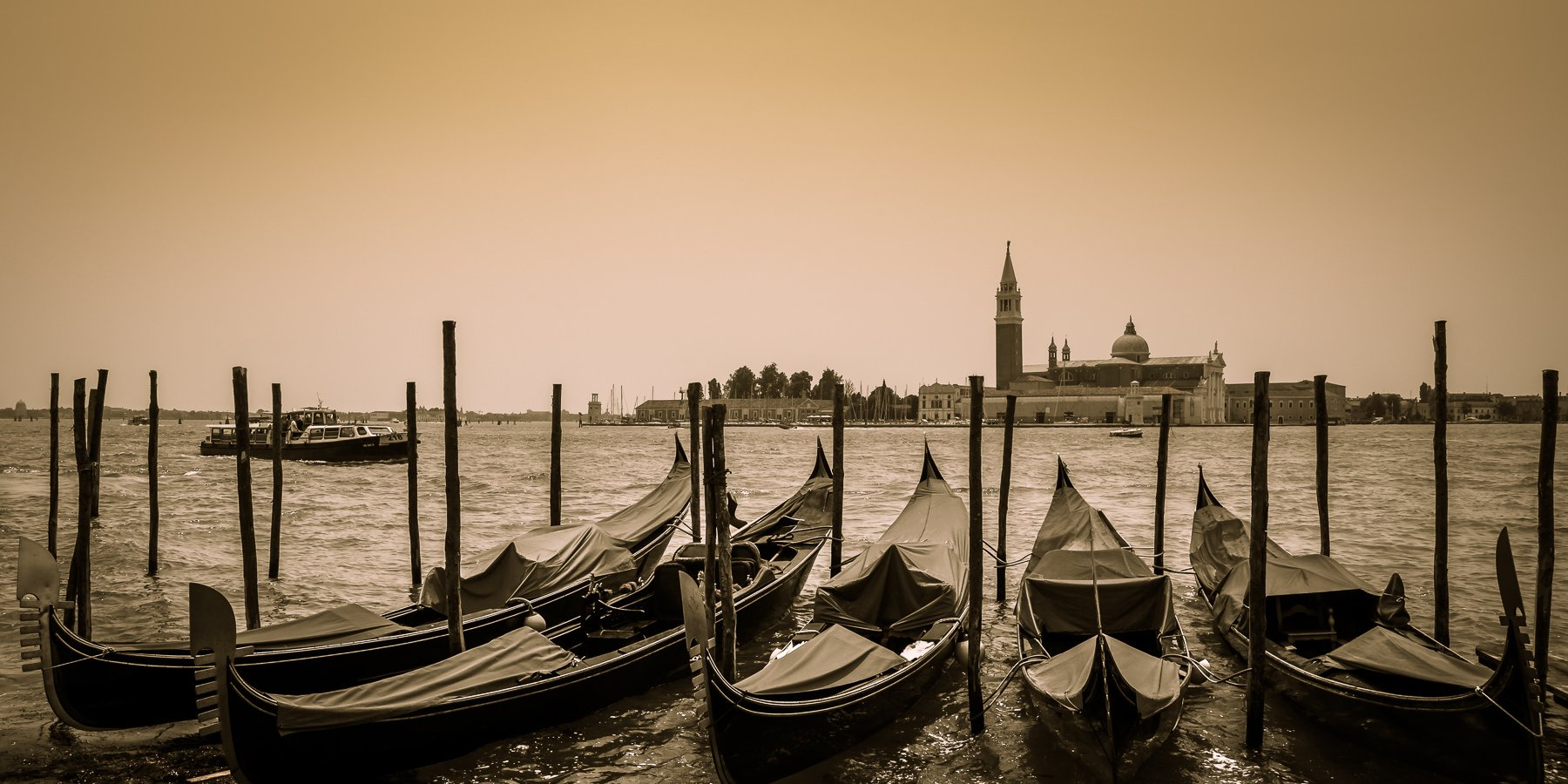 Gondolas tied up looking across the water to San Giorgio Maggiore in Venice, Italy