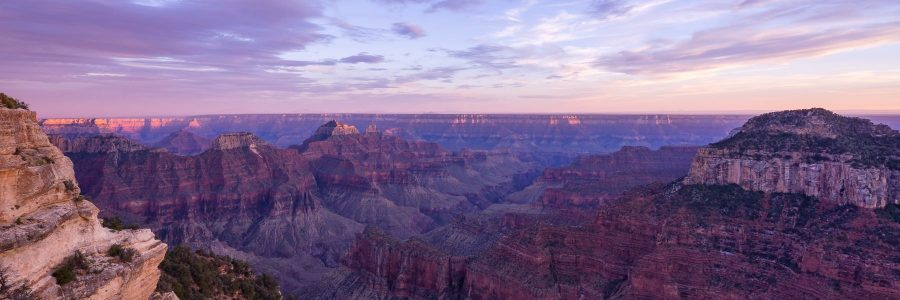 Looking out over the Grand Canyon with sunset lighting the peaks and canyon walls