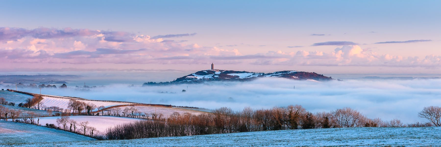Scrabo Tower tasing above the mist at sunset on a winters day