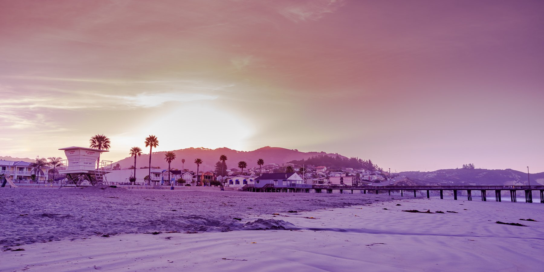 Sunrise over a California Beach with Lifeguard hut and palm trees
