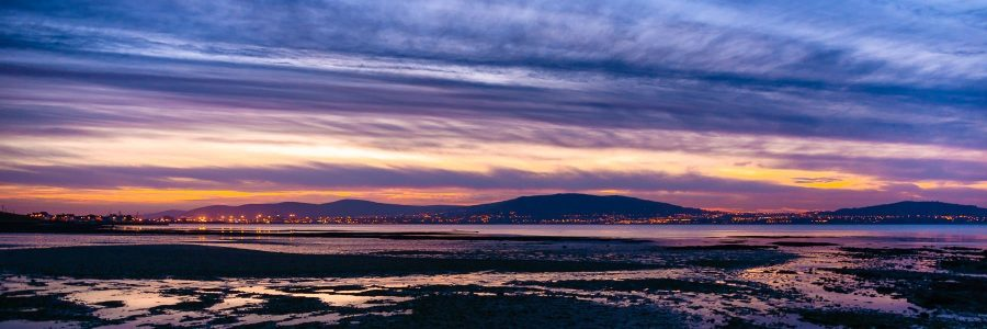 Clouds forming lines in a sunset sky looking over Belfast Lough at the city lights