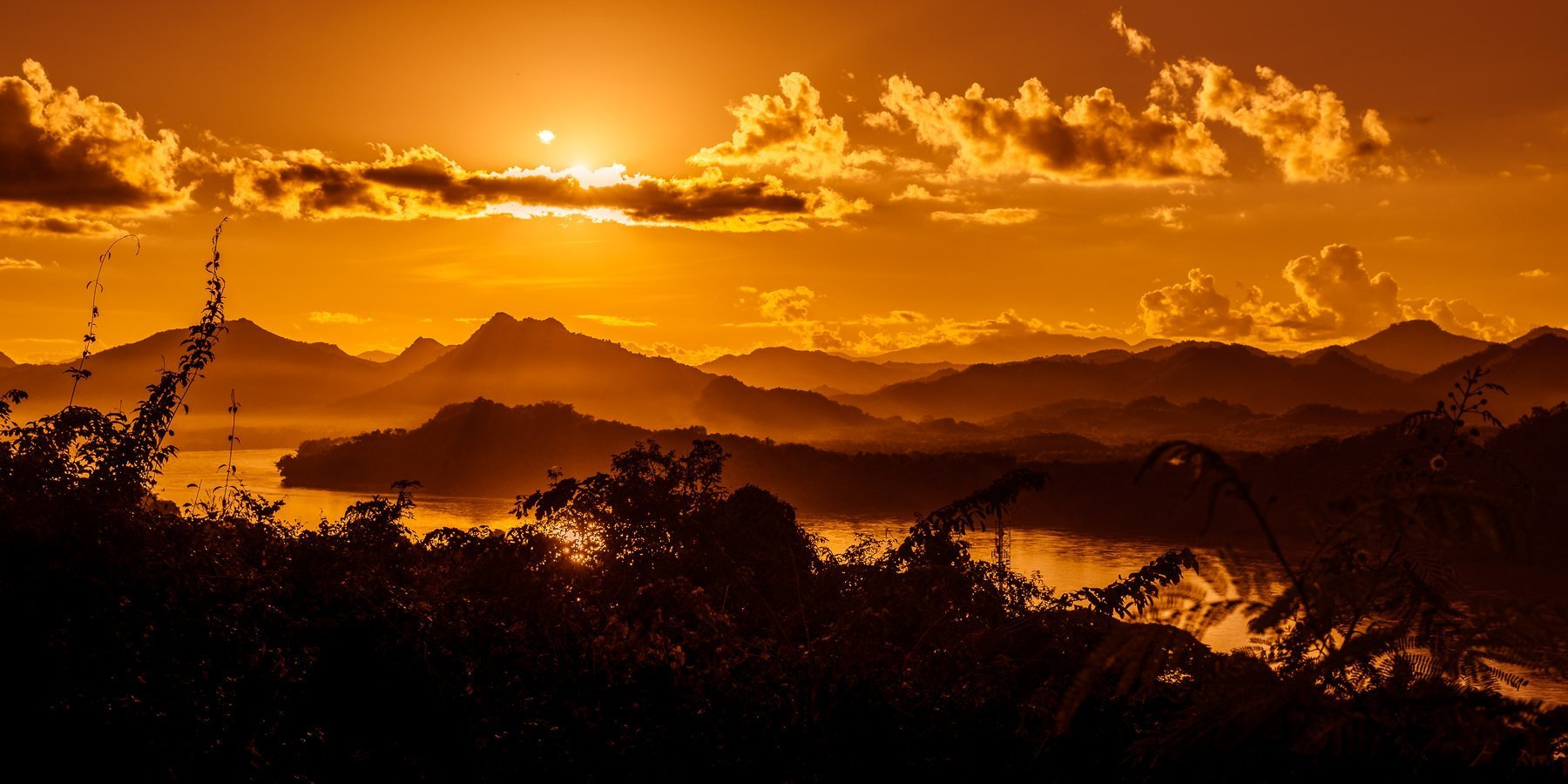 Golden sunlight over the mountainside with the Mekong river winding through the valley in Laos
