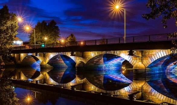 The Ormeau Bridge in Belfast. Its four arches span across the river Lagan and are perfectly reflected in the still water.