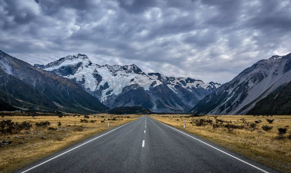 A road in a valley leading towards a snow capped mountain with stormy clouds in the sky