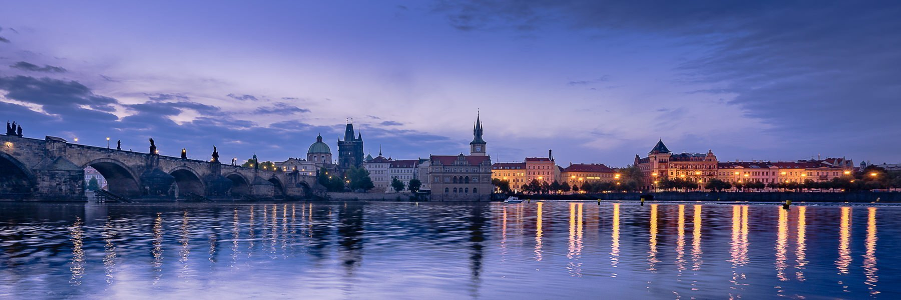 A view looking over the river towards the old town of Prague at blue hour