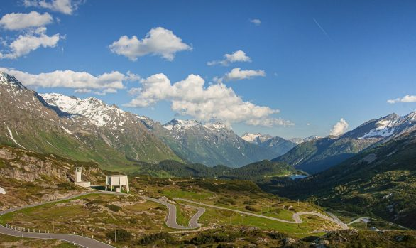 Winding road flowing down a Swiss alpine pass with blue sky and white fluffy clouds