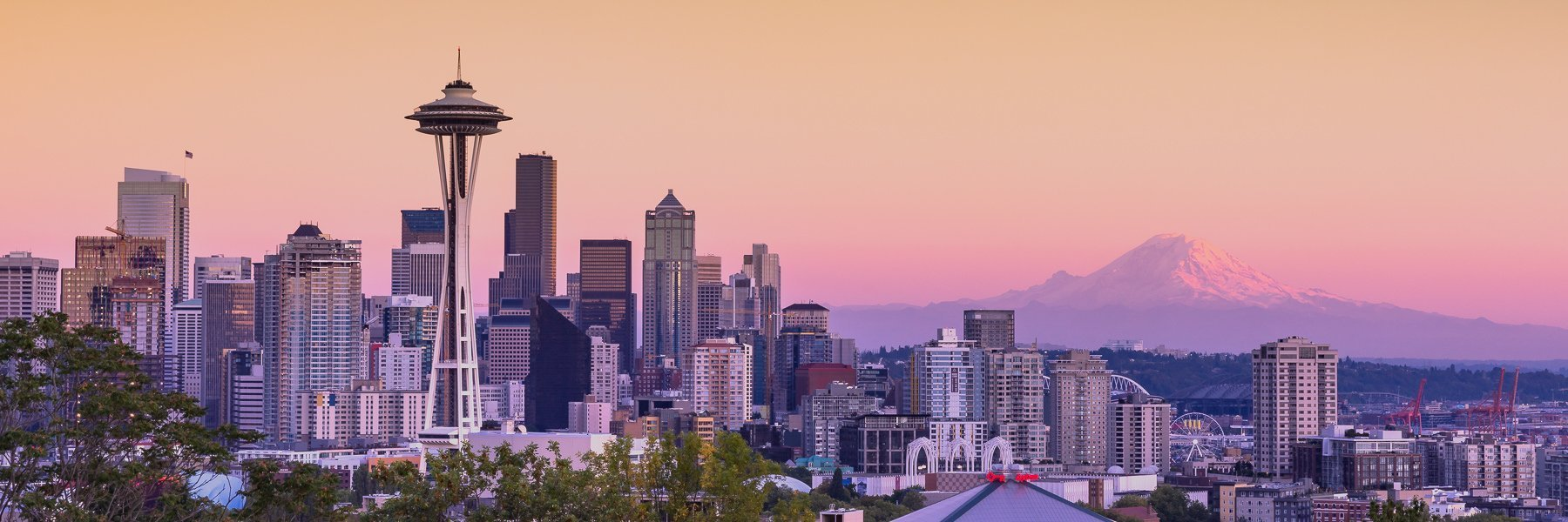 Seattle city skyline with snow capped Mount Rainier in the distance at sunset.