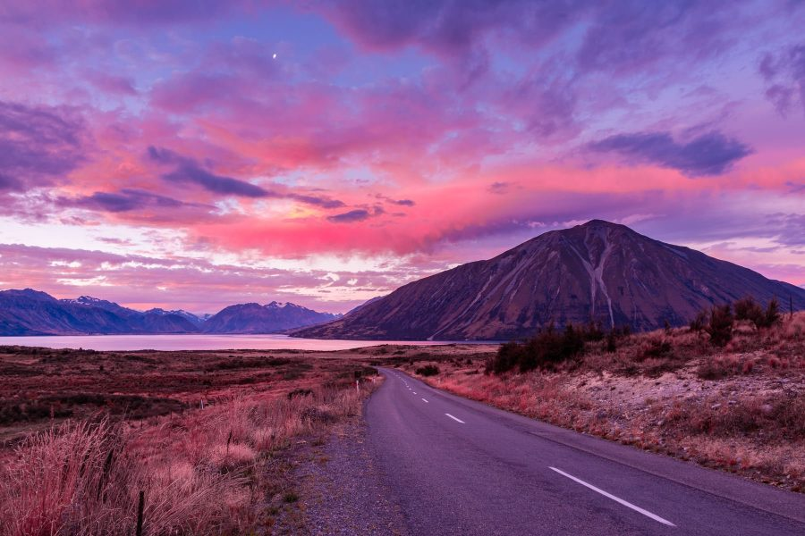 Road leading towards lake with a large mountain with pink and purple clouds the sky
